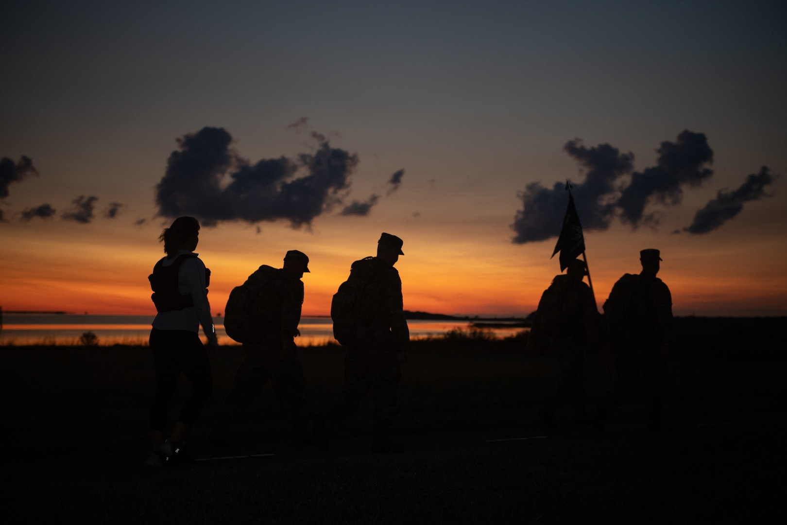 A group of Airmen walk and run outside in an event.