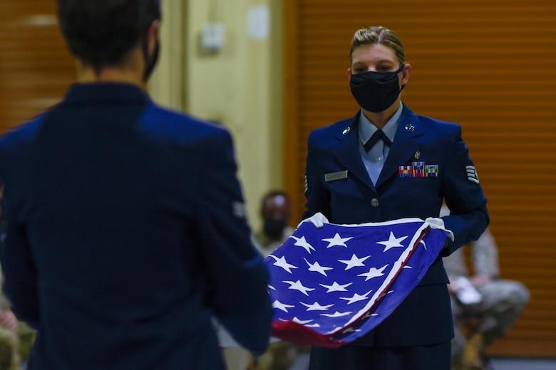 Two Airmen folding a flag.