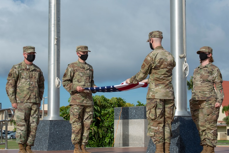 Two airmen fold a flag during a ceremony.