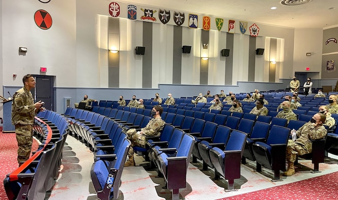 Military doctor speaks to Airmen in an auditorium