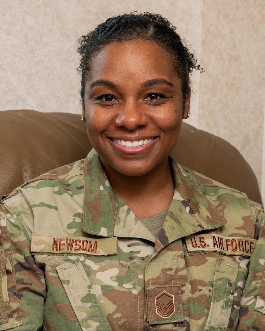 Master Sgt. Keona Newsom, 192nd Operations Group commander's support staff noncommissioned officer in charge, is sitting down and smiling for a photo.