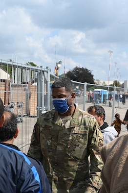 U.S. Air Force Tech. Sgt. Kenton Waring, 435th Air Expeditionary Wing personnel support for contingency operations non-commissioned officer in charge, speaks to evacuees during Operation Allies Refuge at Ramstein Air Base, Germany, Sep. 3, 2021. Over 30,000 evacuees have received support such as temporary lodging, food, medical screening and treatment and more at Ramstein Air Base while preparing for onward movements to their final destinations. (U.S. Air Force photo by Senior Airman Caleb S. Kimmell)