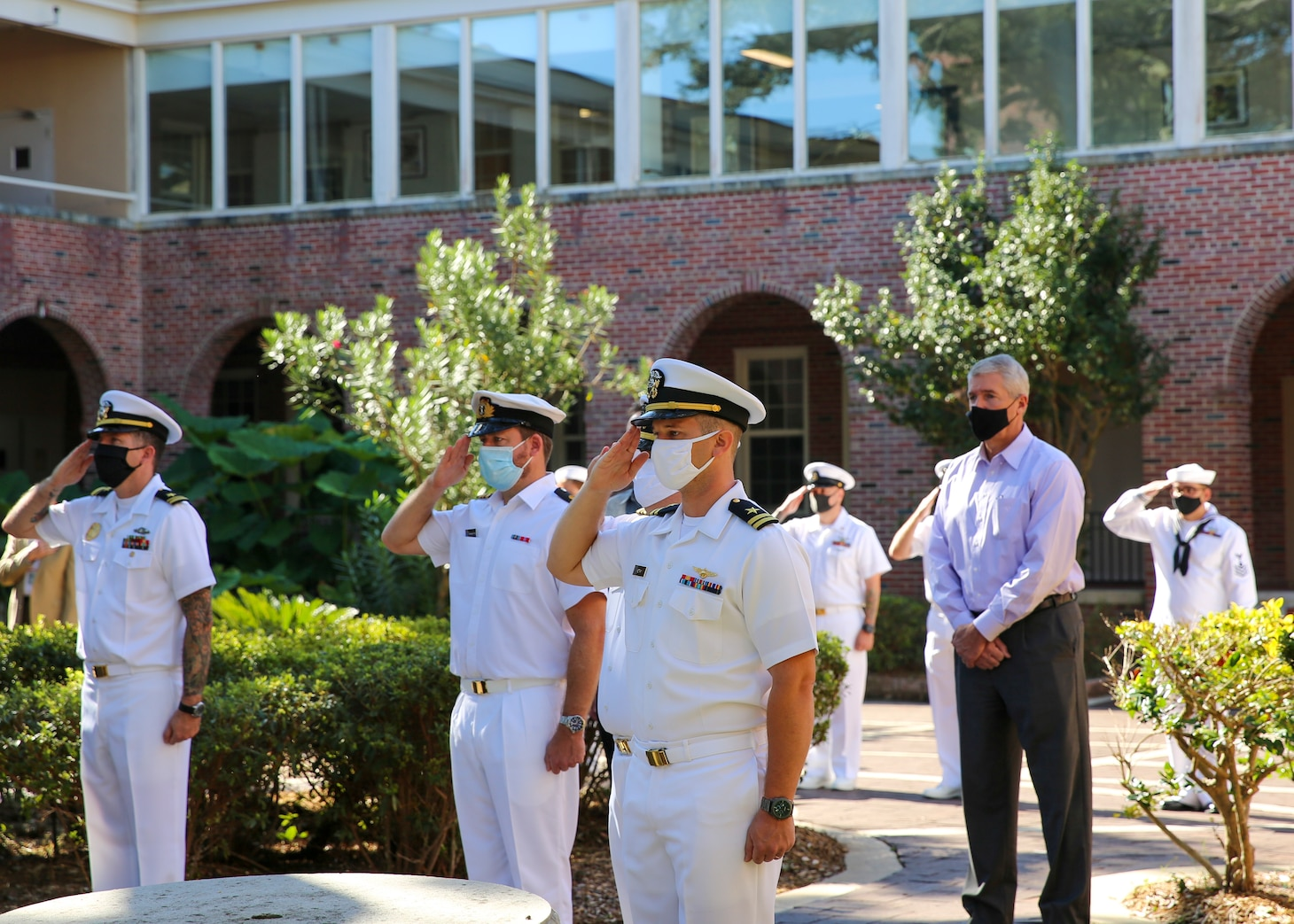 Naval Education and Training Command (NETC) staff members salute as tap plays at the end of a 9/11 memorial ceremony.