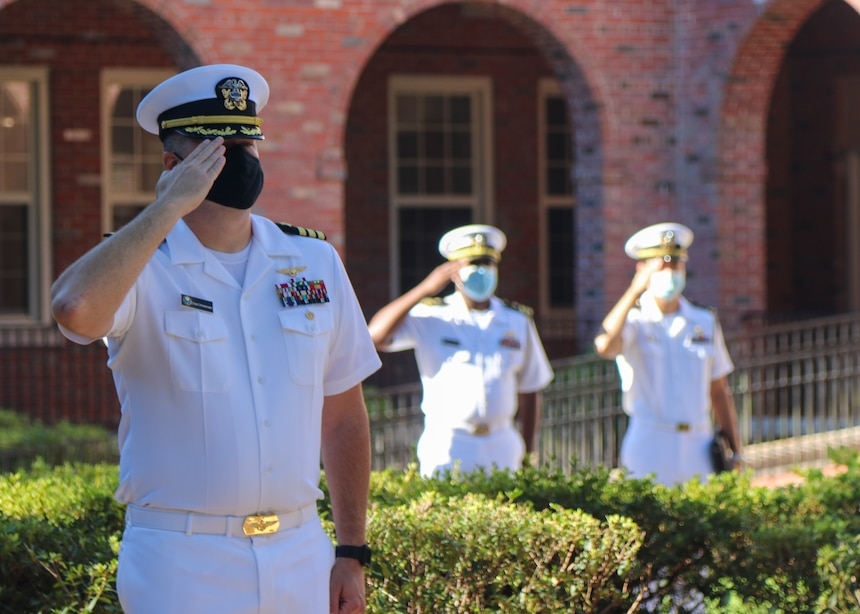 Naval Education and Training Command (NETC) staff members salute as the national anthem plays during a 9/11 memorial ceremony.