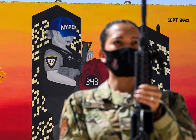 U.S. Air Force Staff Sgt. Aubrey Houston, 378th Expeditionary Security Forces Squadron defender, posts with her weapon in front of a memorial mural during the playing of the national anthem in a Remembrance Ceremony Sept. 11, 2021, at Prince Sultan Air Base, Kingdom of Saudi Arabia.
