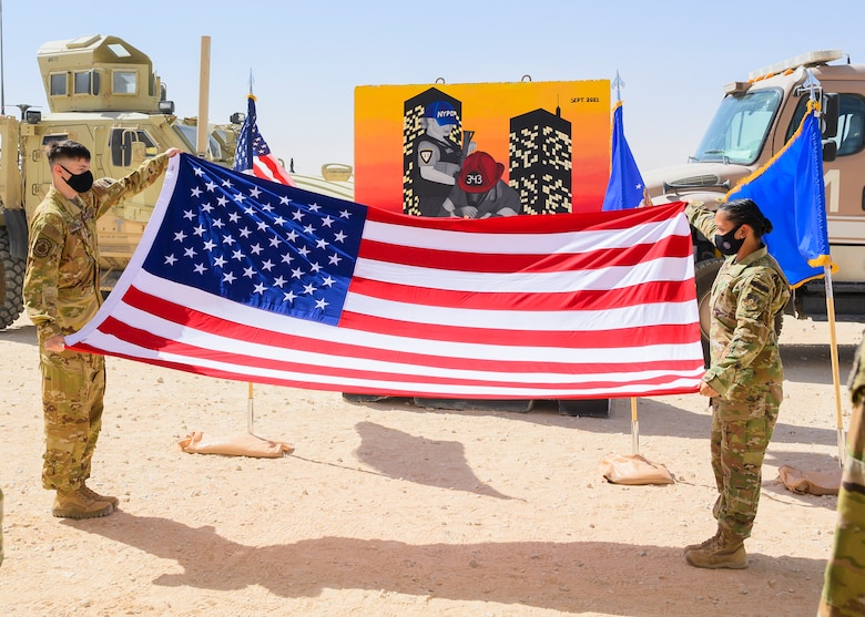 Airman 1st Class Timothy Treat-Mass, 378th Expeditionary Civil Engineer Squadron firefighter, and Staff Sgt. Aubrey Houston, 378th Expeditionary Security Forces Squadron defender, prepare to fold the flag during a Remembrance Ceremony Sept. 11, 2021, at Prince Sultan Air Base, Kingdom of Saudi Arabia.