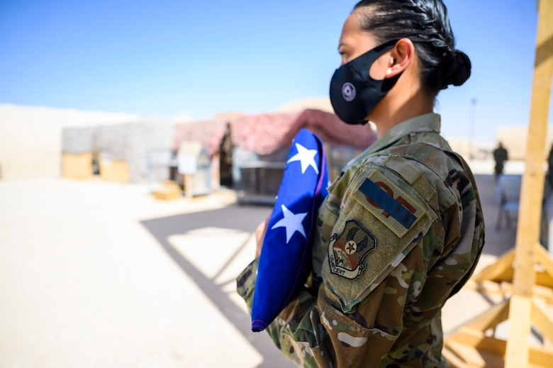 Staff Sgt. Aubrey Houston, 378th Expeditionary Security Forces Squadron defender, holds the flag during a Remembrance Ceremony Sept. 11, 2021, at Prince Sultan Air Base, Kingdom of Saudi Arabia.