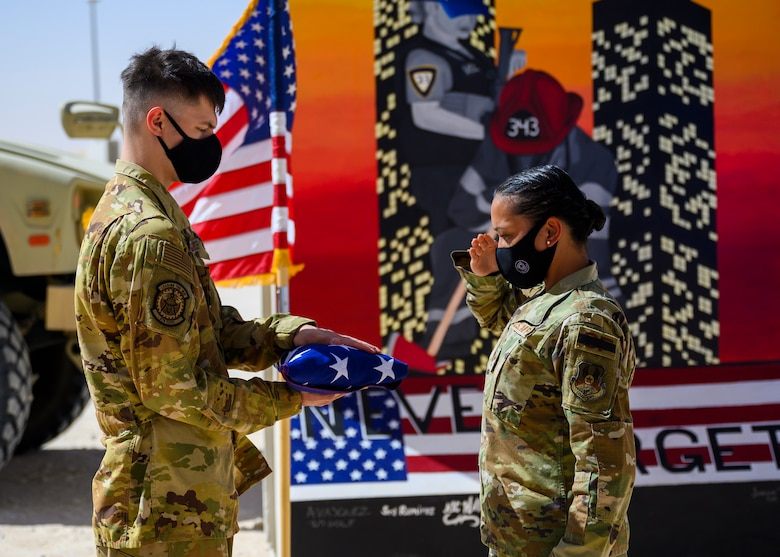 Staff Sgt. Aubrey Houston, 378th Expeditionary Security Forces Squadron defender, salutes the flag as it is held by Airman 1st Class Timothy Treat-Mass, 378th Expeditionary Civil Engineer Squadron firefighter, during a Remembrance Ceremony Sept. 11, 2021, at Prince Sultan Air Base, Kingdom of Saudi Arabia.