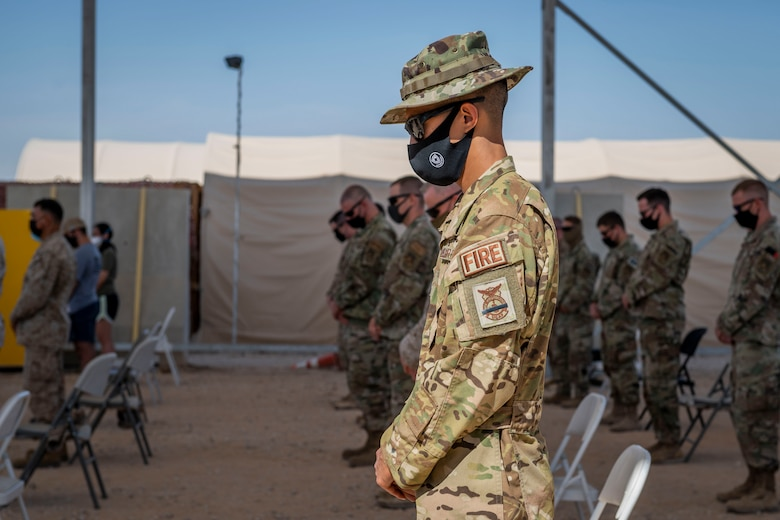 Members of the 378th Air Expeditionary Wing stand for prayer during a Remembrance Ceremony Sept. 11, 2021, at Prince Sultan Air Base, Kingdom of Saudi Arabia.