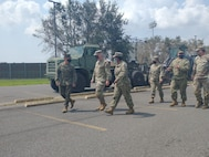Brig. Gen. Kelliher, Officer in Charge of JFLCC Forward Command Element, and Brig. Gen Prendergast, commander of Task Force 51, discuss current operations with LT Jasmine Aldino and Senior Chief Construction (SCW/EXW) Jason Fletcher around the equipment staging area for DSCA operations in response to Hurricane Ida relief efforts. (Released/U.S. Marine Corps photo by 1st Lt. Aaron Ladd)