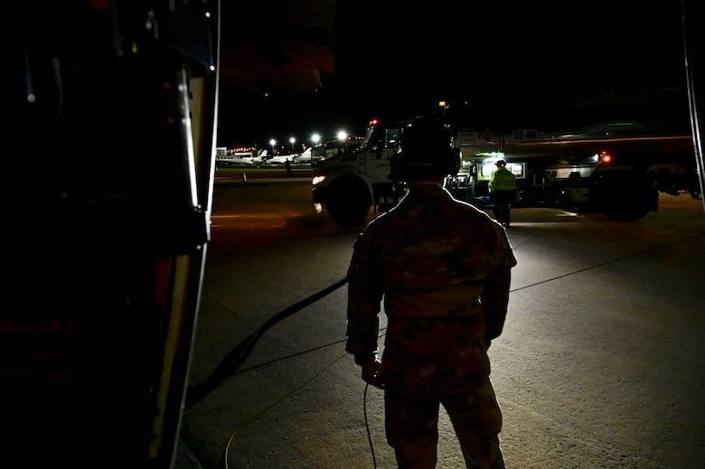 An Airmen watches as a C-130J is refueled