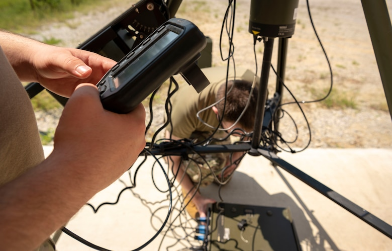 An airman tightens power cables on a tactical meteorological observing system