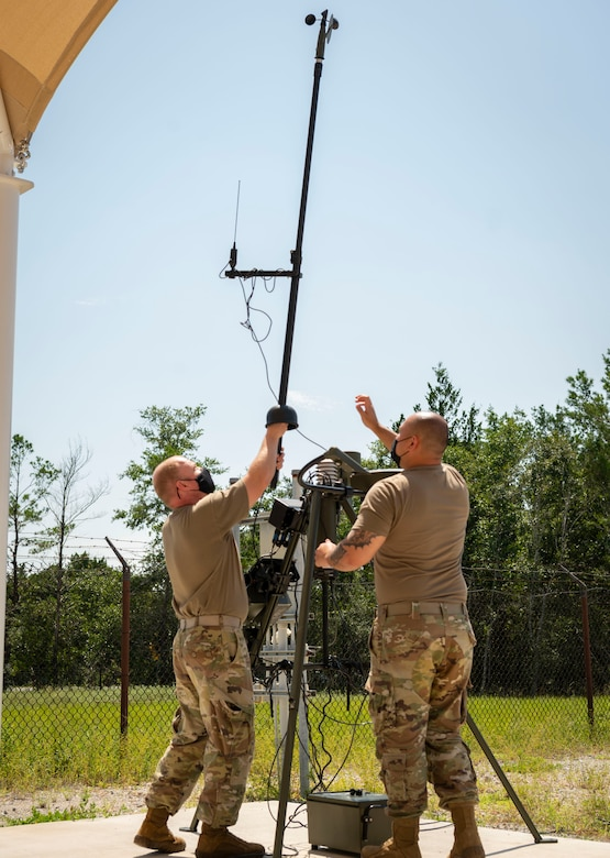 Two Airmen work together to take the mast off a tactical meteorological observing system