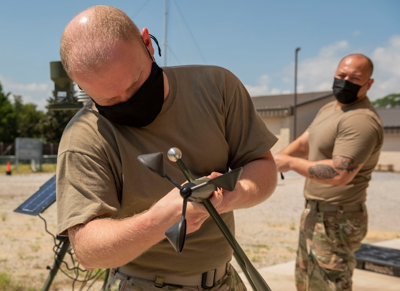 Two Airmen work together to fix a wind sensor on a tactical meteorological observing system