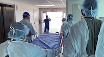 An Army Forward Resuscitative Surgical Team (FRST) prepares to receive a trauma patient as part of trauma scenario training provided by the Army Trauma Training Detachment and Ryder Trauma Center at Jackson Memorial in Miami, Florida, during pre-deployment training August 2021.