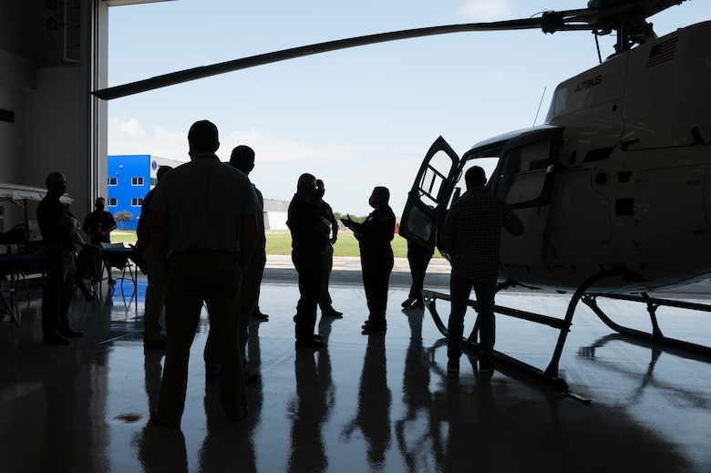 A group of people stand near a H-125 helicopter.