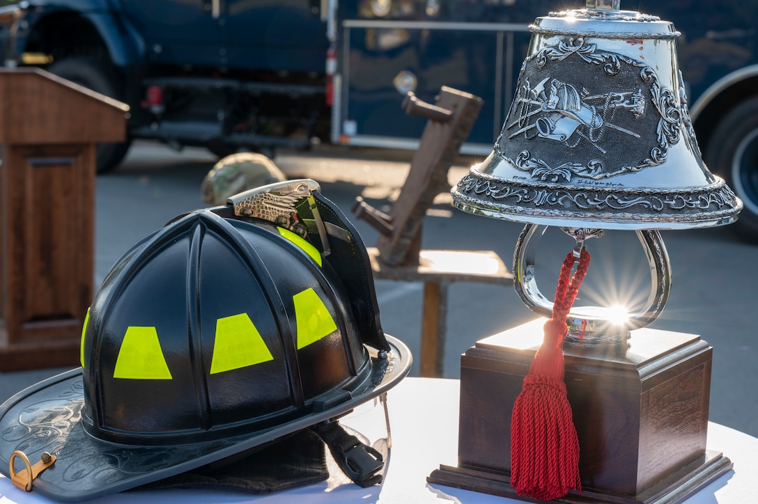 A firefighter helmet and bell are on display on a table