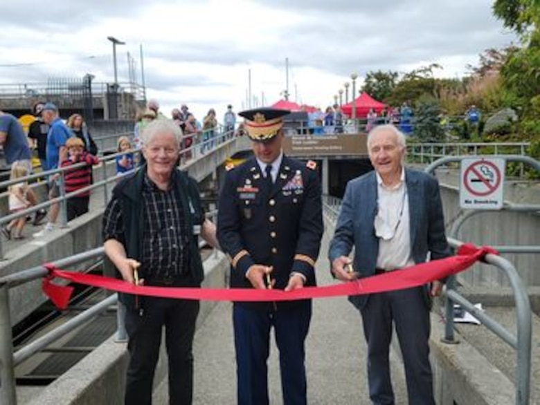 Photo of Executive Director of Discover Your Northwest, Jim Adams, Col. Alexander 'Xander' Bullock, USACE Seattle district commander, and Rich Deline, director of The Corps Foundation, cutting the red ribbon to officially open the newly renovated fish ladder viewing room to the public, at Lake Washington Ship Canal and Hiram M. Chittenden Locks, Aug. 16, 2021.