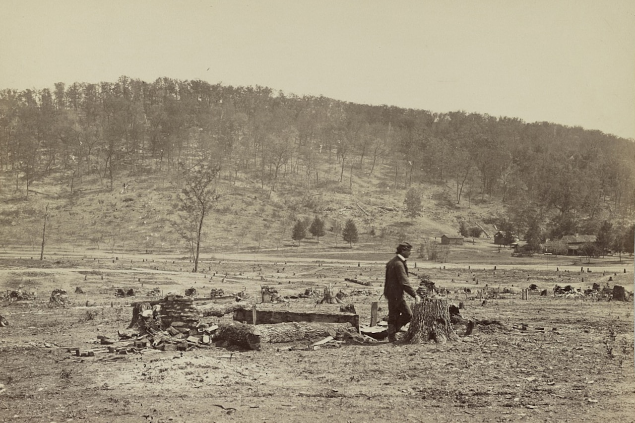 A man walks past debris in an open field. A wooded hill is in the background.