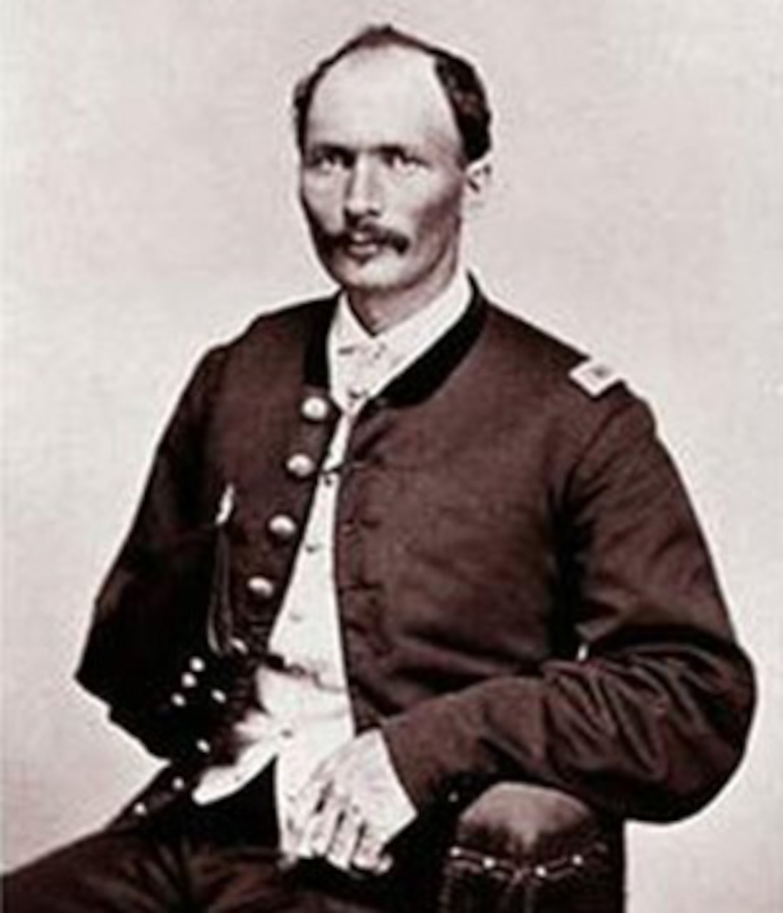 A soldier in a Civil War-era uniform sits for a photo.