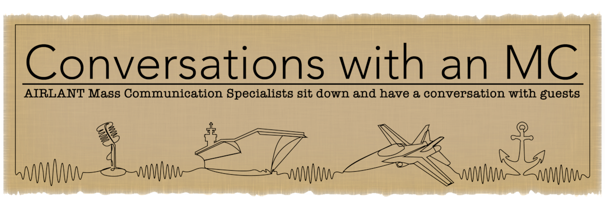 Banner depicting a microphone, aircraft carrier, jet and anchor