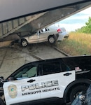 A vehicle is wedged under an overpass off of I-35 in Minnesota after it crashed Aug. 20, 2021. Minnesota National Guard 1st Sgt. Christopher Reed, the joint operations center noncommissioned officer in charge and first sergeant of Headquarters and Headquarters Company, 1st Armored Brigade Combat Team, 34th Red Bull Infantry Division, helped the two passengers, who were OK.