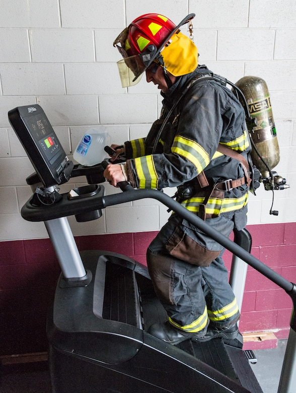 Tech. Sgt. Drew Thatcher, 436th Civil Engineer Squadron fire prevention noncommissioned officer in charge, climbs on a stair machine on Dover Air Force Base, Delaware, Sept. 9, 2021. Wearing fire protection gear, Thatcher climbed 110 stories, the same amount as the World Trade Center towers. (U.S. Air Force photo by Roland Balik)