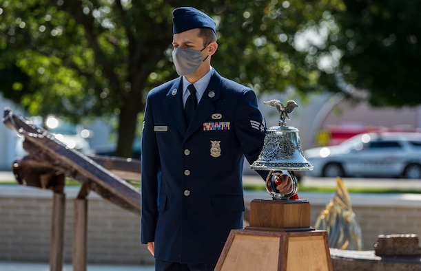 """Senior Airman Kyle Spence, 436th Civil Engineer Squadron fire department operator, performed  """"Striking the Four Fives"""" during the 20th Anniversary 9/11  Remembrance Ceremony held at the Air Mobility Command Museum's 9/11 Memorial on Dover Air Force Base, Delaware, Sept. 11, 2021. Spence rang the bell five times, for four sets, to honor the 343 firefighters who died while responding to the terrorist attacks on the World Trade Center in New York Sept. 11, 2001. (U.S. Air Force photo by Roland Balik)"""