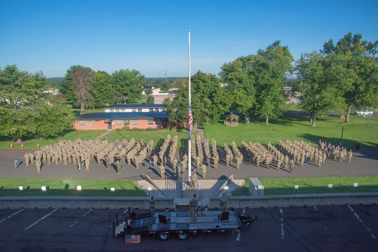 An Air Force Wing stands in formation outside near a flag pole.