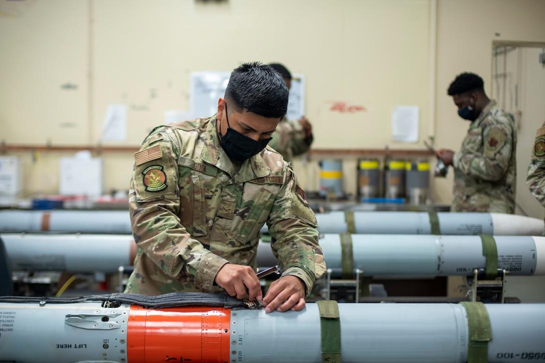 Man uses a tool to secure a spacer on a missile