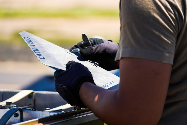 Senior Airman Paulo Amaya, 15th Aircraft Maintenance Squadron weapons load crew member, prepares a fin to be installed on a Captive Air Training Missile AIM-120 during an Agile Combat Employment training exercise at Pacific Missile Range Facility Barking Sands, Hawaii, September 8, 2021. The ACE concept utilizes Multi-Capable Airmen to refuel, rearm, and perform maintenance to fighter jets ensuring the aircraft are ready to rapidly deploy. (U.S. Air Force photo by Airman 1st Class Makensie Cooper)