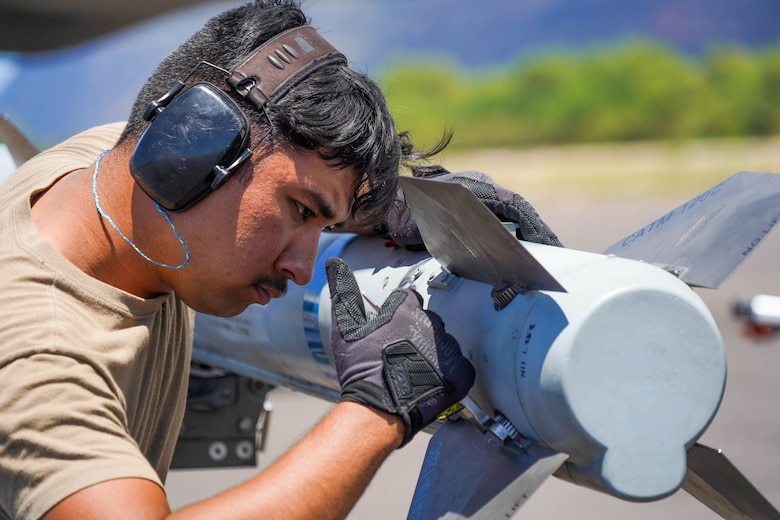 Senior Airman Paulo Amaya, 15th Aircraft Maintenance Squadron weapons load crew member,  tightens a fin on a Captive Air Training Missile AIM-120 during an Agile Combat Employment training exercise at Pacific Missile Range Facility Barking Sands, Hawaii, September 8, 2021. The ACE concept utilizes Multi-Capable Airmen to refuel, rearm, and perform maintenance to fighter jets ensuring the aircraft are ready to rapidly deploy. (U.S. Air Force photo by Airman 1st Class Makensie Cooper)