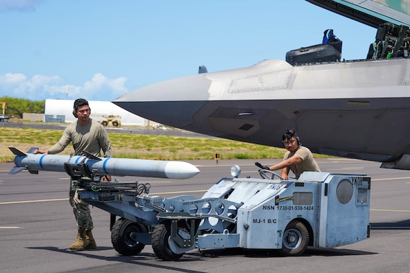 Staff Sgt. Tom Savea, 154th Aircraft Maintenance Squadron loading standardization crew member, and Senior Airman Paulo Amaya, 15th Aircraft Maintenance Squadron weapons load crew member, prepare an AIM-120 missile to be loaded onto an F-22 Hawaiian Raptor during an Agile Combat Employment training exercise at Pacific Missile Range Facility Barking Sands, Hawaii, September 8, 2021. The ACE exercise demonstrated Multi-Capable Airmen's ability to refuel, and rearm in different locations to ensure a free and open Indo-Pacific. (U.S Air Force photo by Airman 1st Class Makensie Cooper)