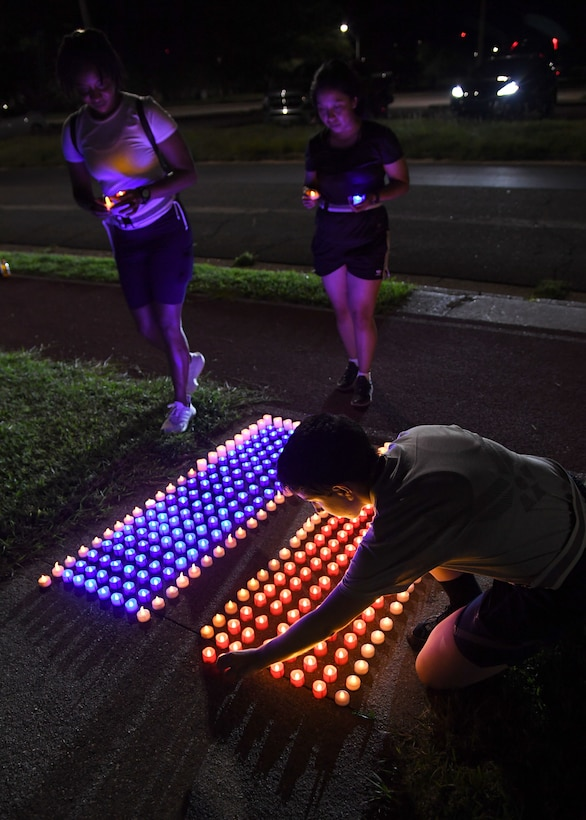 U.S. Air Force Airman 1st Class Halimatou Diallo and Airman Karla Monroy, 335th Training Squadron students, and Airman 1st Class Emily Kalman, 338th Training Squadron student, place flameless candles on the ground outside of Stennis Hall during the 2nd Annual 9/11 Memorial Run at Keesler Air Force Base, Mississippi, Sept. 10, 2021. The 24-hour run honored those who lost their lives during the 9/11 attacks. (U.S. Air Force photo by Kemberly Groue)