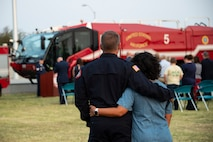 Philip Fourroux, 97th Civil Engineer Squadron installation fire chief, left, and his wife comfort each other during the 97th Air Mobility Wing Remembrance Ceremony at Altus Air Force Base, Oklahoma, Sept. 11, 2021. This is the tenth year the base has held a 9/11 memorial ceremony as a wing-level event for all Airmen. (U.S. Air Force photo by Senior Airman Amanda Lovelace)