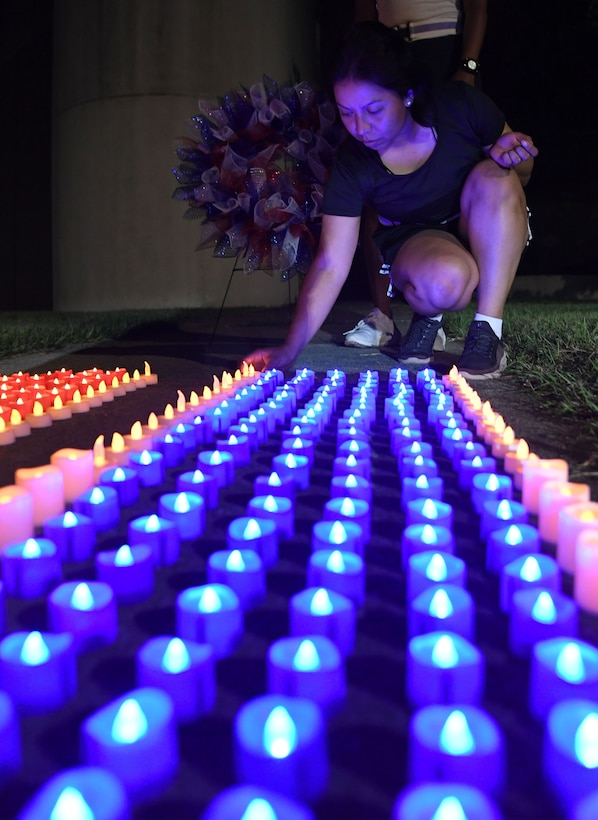 U.S. Air Force Airman Basic Karla Monroy, 335th Training Squadron student places a flameless candle on the ground outside of Stennis Hall during the 2nd Annual 9/11 Memorial Run at Keesler Air Force Base, Mississippi, Sept. 10, 2021. The 24-hour run honored those who lost their lives during the 9/11 attacks. (U.S. Air Force photo by Kemberly Groue)