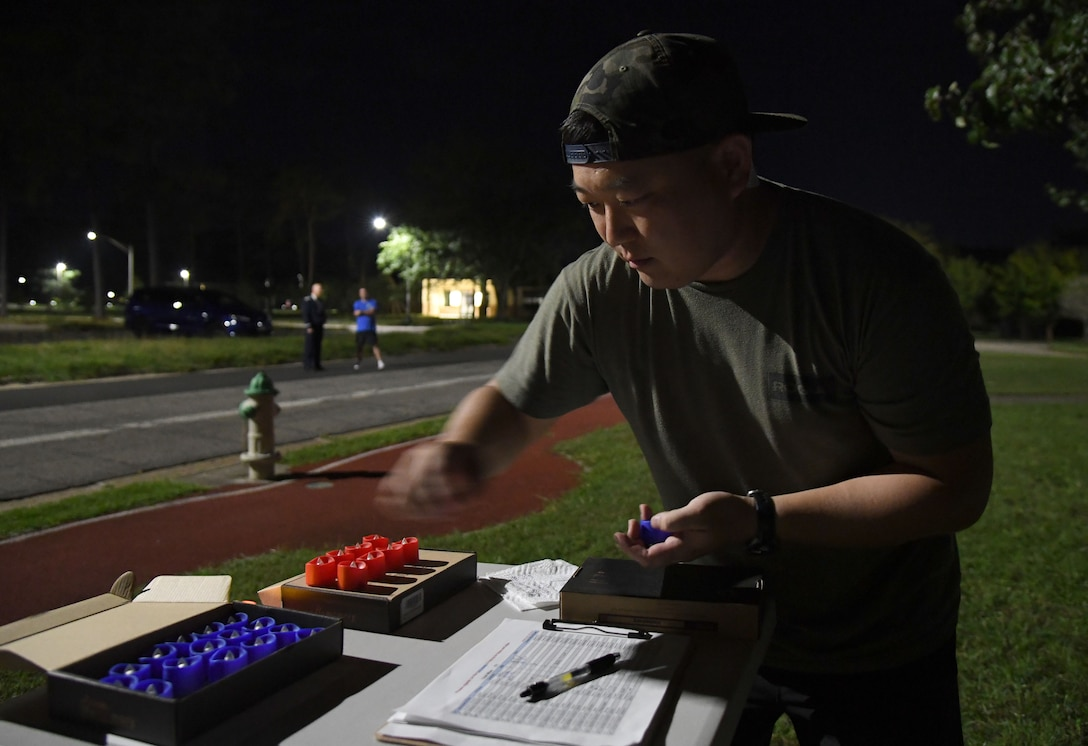 U.S. Air Force 2nd Lt. James Ro, 333rd Training Squadron student, prepares flameless candles for runners outside of Stennis Hall during the 2nd Annual 9/11 Memorial Run at Keesler Air Force Base, Mississippi, Sept. 10, 2021. The 24-hour run honored those who lost their lives during the 9/11 attacks. (U.S. Air Force photo by Kemberly Groue)