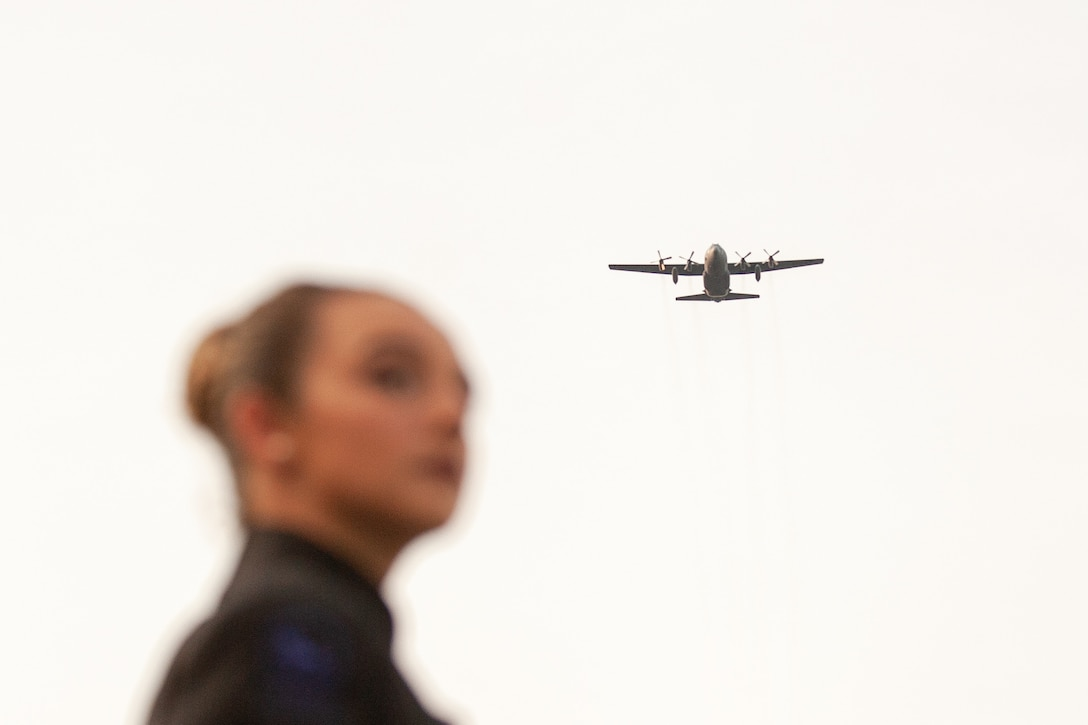 woman looks on as a c-130 approaches