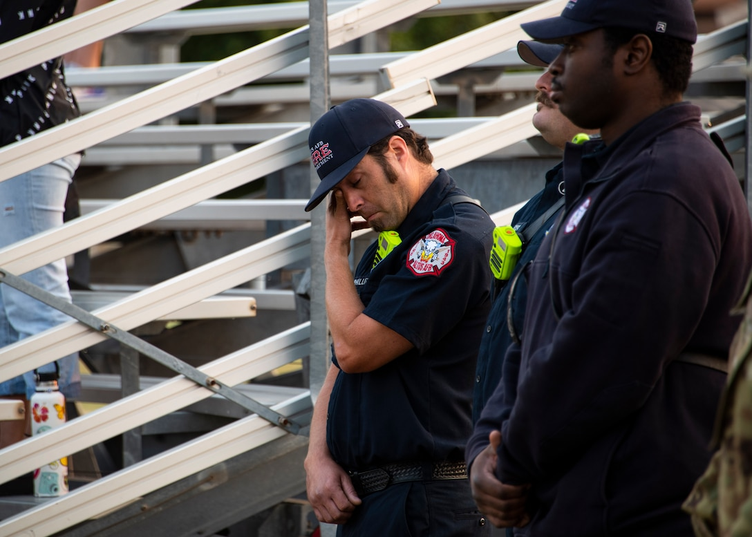 """Josh Phillips, 97th Civil Engineer Squadron firefighter, left, wipes tears from his eyes as """"Amazing Grace"""" plays during the 97th Air Mobility Wing Remembrance Ceremony at Altus Air Force Base, Oklahoma, Sept. 11, 2021. This year marks 20 years since the 9/11 attacks. (U.S. Air Force photo by Senior Airman Amanda Lovelace)"""