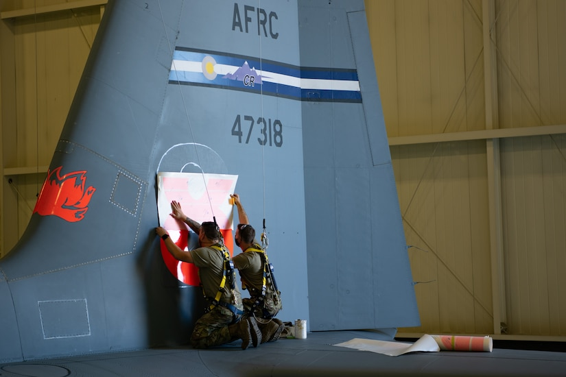 Two maintainers wearing fall restraint harnesses standing on the tail of a C-130 aircraft apply a large orange 8 to the aircraft.