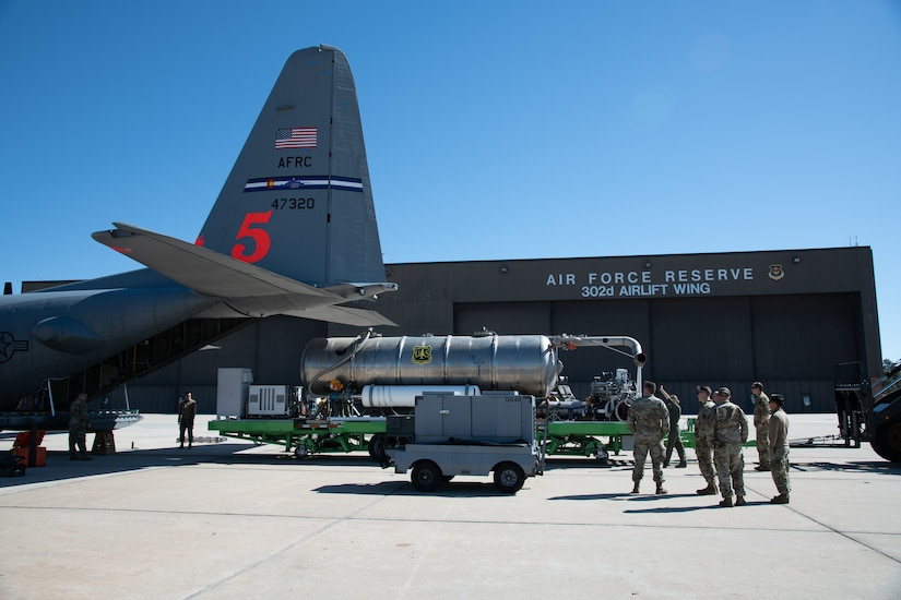 Airmen load a large metal storage unit with a U.S. Forest Service label on it into the back of a C-130 aircraft.