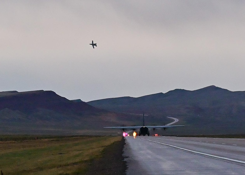 A fighter aircraft in the air above a cargo reversing down a highway