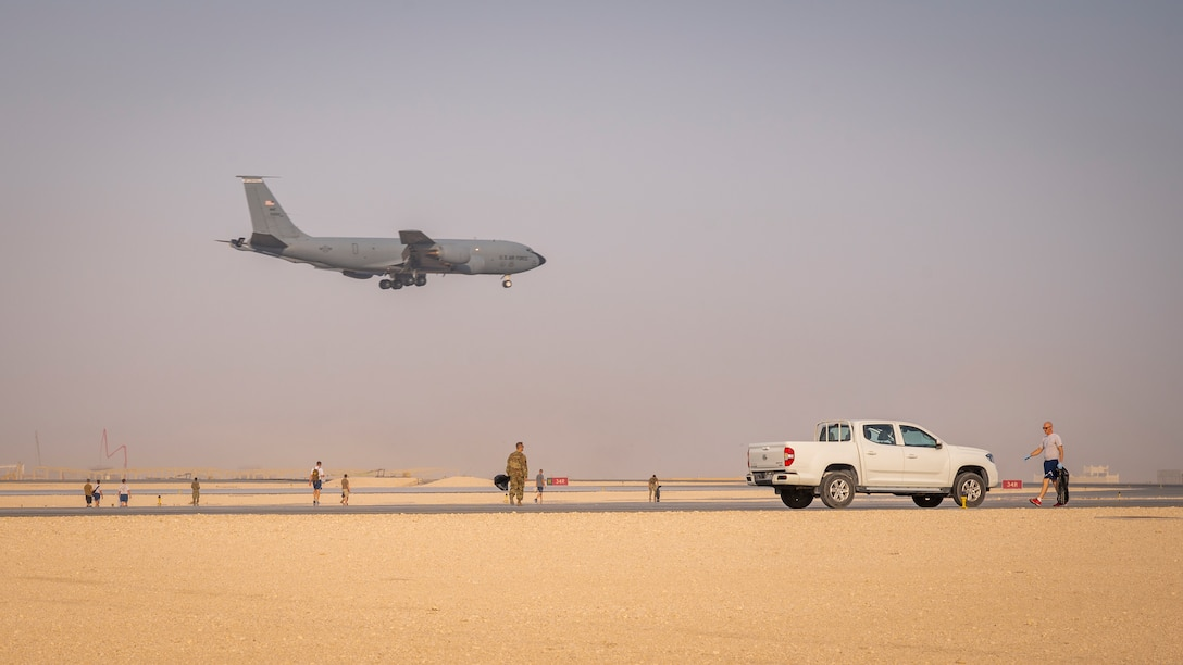 A KC-135 Stratotanker jet lands on the runway as service members conduct a foreign object debris walk Sept. 8, 2021, at Al Udeid Air Base, Qatar.