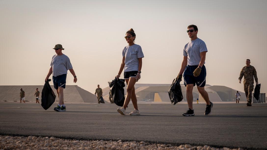 Service members walk across a taxiway on the flightline Sept. 8, 2021, at Al Udeid Air Base, Qatar.