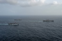 ARABIAN SEA (September 13, 2021) Amphibious assault ship USS Essex (LHD 2), right, amphibious dock landing ship USS Pearl Harbor (LSD 52), front, and amphibious transport dock ship USS Portland (LPD 27), transit the Arabian Sea, Sept. 13. The Essex Amphibious Ready Group is deployed to the U.S. 5th Fleet area of operations to ensure maritime stability and security in the Central Region, connecting the Mediterranean and the Pacific through the western Indian Ocean and three strategic choke points.