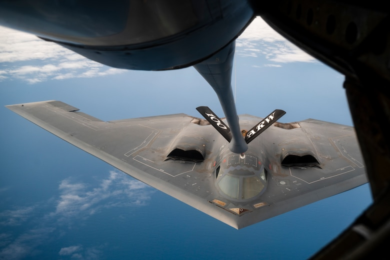 A U.S. Air Force B-2 Spirit flies above the Atlantic Ocean while a U.S. Air Force KC-135 flies above it. The refueling boom is visible and connected to the B-2.