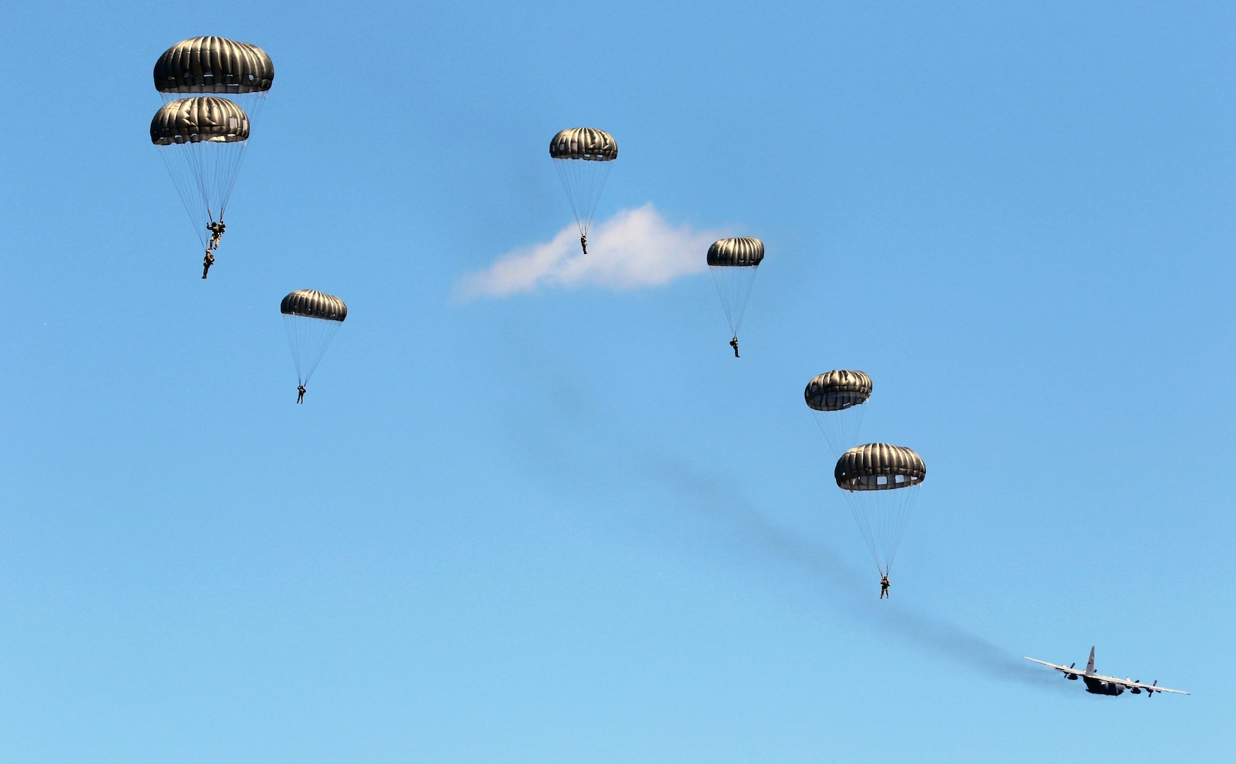 Soldiers with the 294th Quartermaster Company, 338th Quartermaster Company, Texas Army National Guard, the 3rd Special Forces Group, soldiers with the Latvian Army's Special Forces Group and British Army's 4th Battalion, Parachute Regiment (4 PARA), jump out of a C-130 Hercules aircraft over Camp Grayling Joint Maneuver Training Center, Grayling, Michigan, Aug. 13, 2021. The service members conducted joint airborne training during Northern Strike 21.
