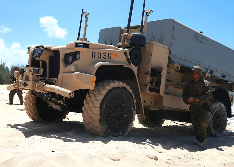 An artillery Marine from 1st Battalion, 12th Marines maneuvers a Navy Marine Expeditionary Ship Interdiction System launcher across the beach aboard Pacific Missile Range Facility Barking Sands, Hawaii, Aug. 16, 2021. During Large Scale Exercise 2021, the Marines of 1/12 struck a naval target ship with two Naval Strike Missiles which flew more than 100 nautical miles before striking the ship. LSE 2021 allowed Marines to refine concepts such as expeditionary advanced base operations and littoral operations in a contested environment in order to provide sea control or contribute to sea denial near key maritime terrain.