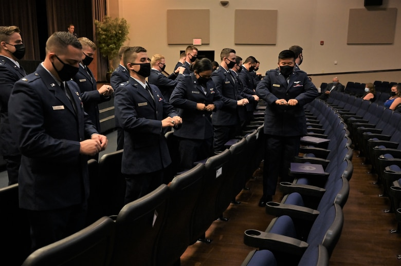 Graduates from Specialized Undergraduate Pilot Training class 21-15, break their first pair of wings during the graduation ceremony, Sept. 10, 2021, on Columbus Air Force Base, Miss. Per tradition, pilots will keep one half of the broken wings and give the second half to a loved one. The two halves are never to be brought back together while the pilot is still alive. (U.S. Air Force photo by Senior Airman Jake Jacobsen)