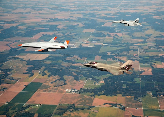 An unmanned Boeing MQ-25 T1 Stingray test aircraft, left, refuels a manned F-35 Lightning II.